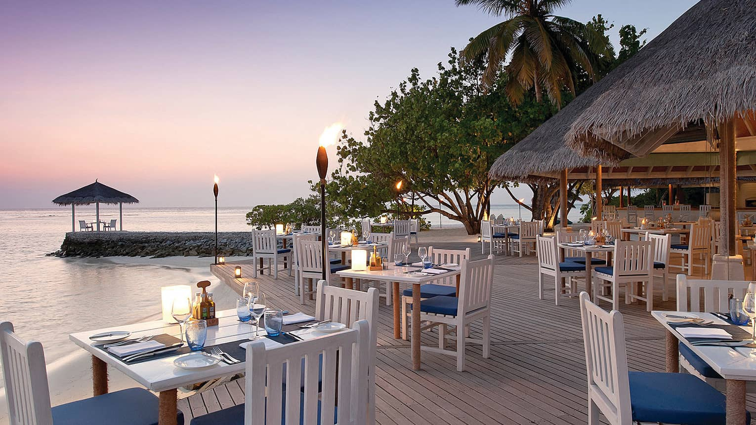 Reef Club on the water at sunset, with white tables on open patio and torches