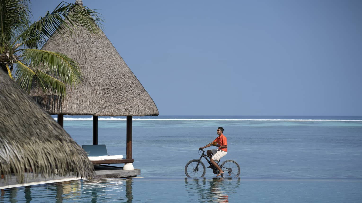 Man riding bicycle in shallow water, view of vast sea behind him