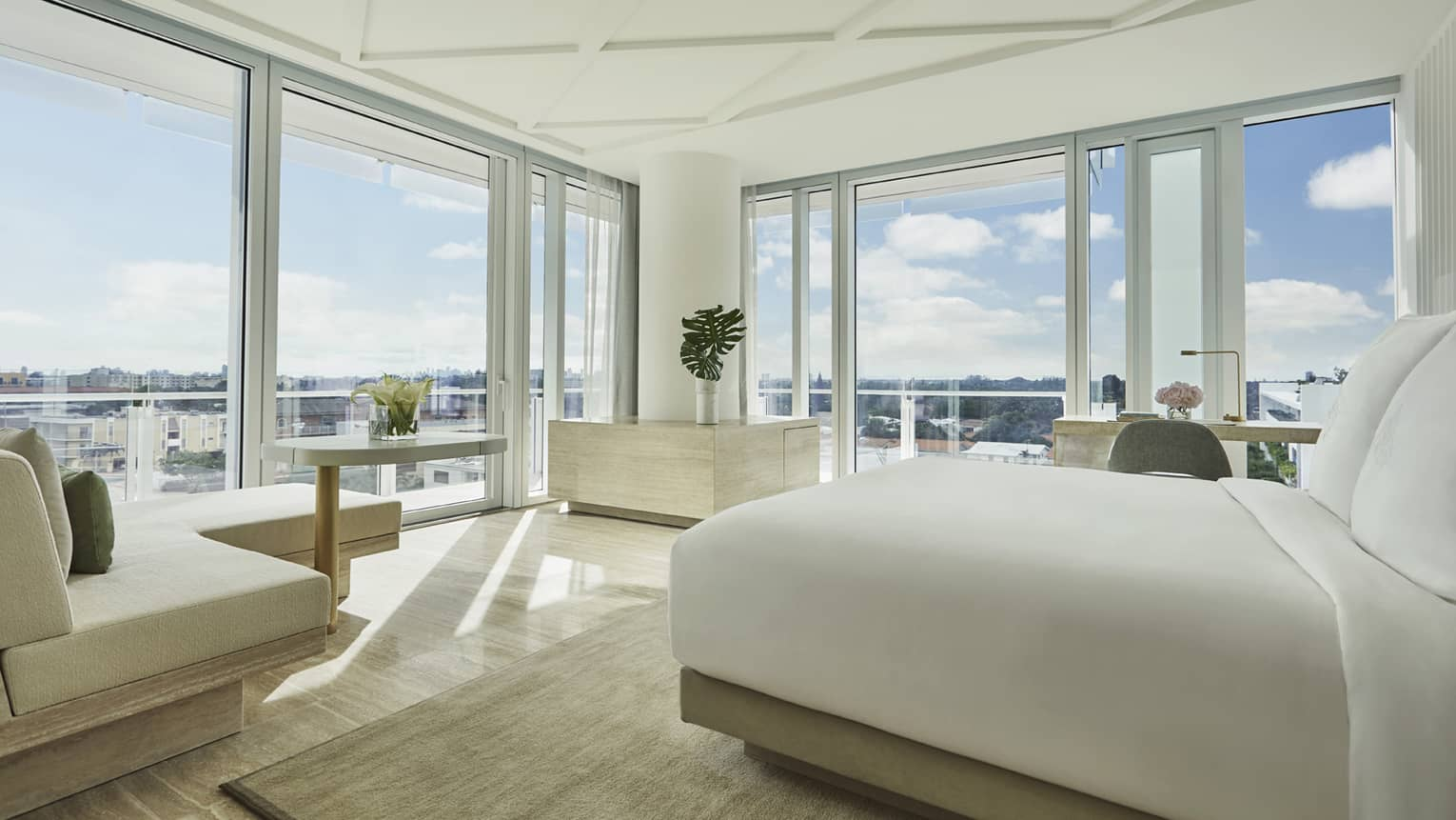 Sunset Studio Suite with modern white bed and chaise, and floor-to-ceiling windows with expansive views