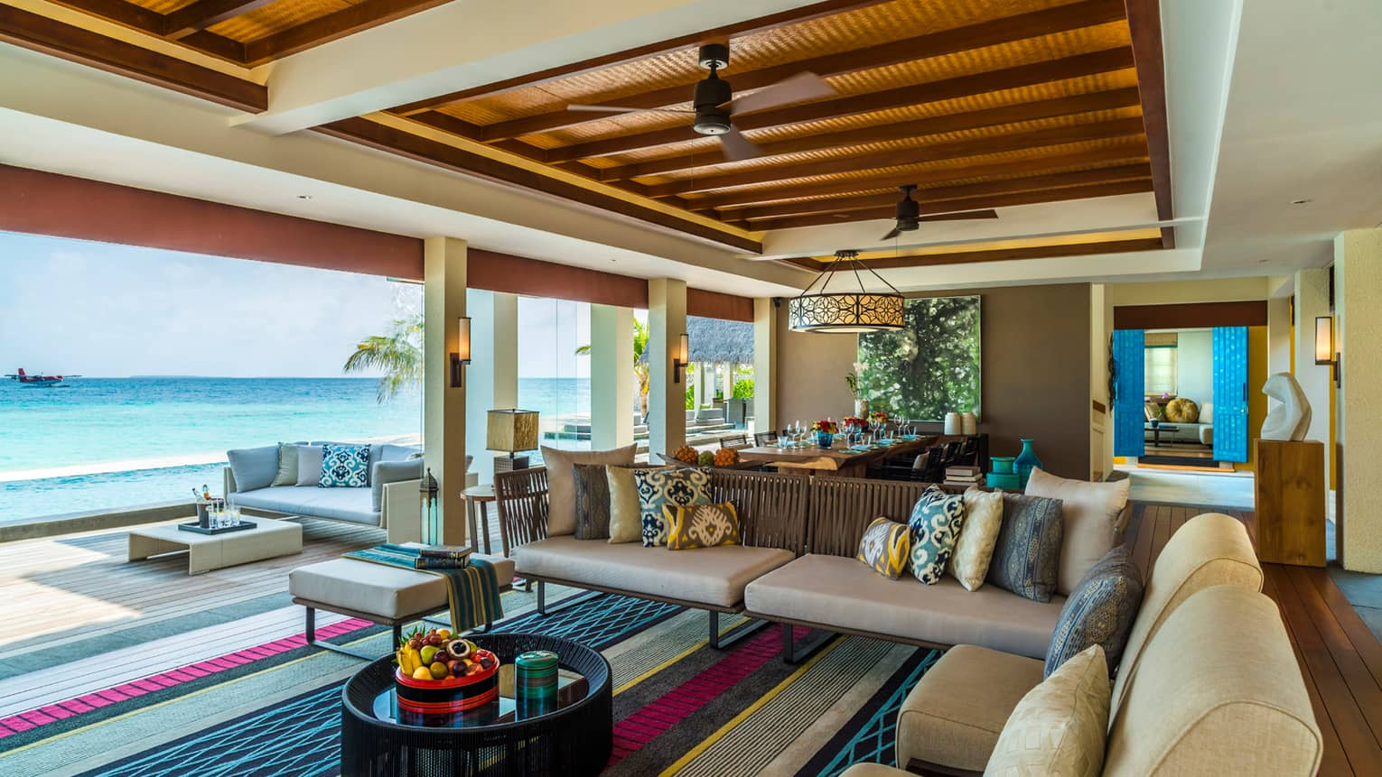 Three-Bedroom Landaa Estate open-air living room sofas, chairs looking out at ocean