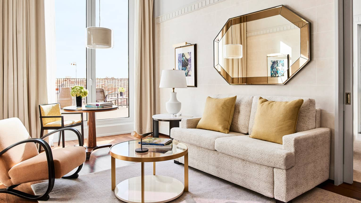 Living room with two-seat sofa, gold mirror, arm chair, round glass table, doors to terrace
