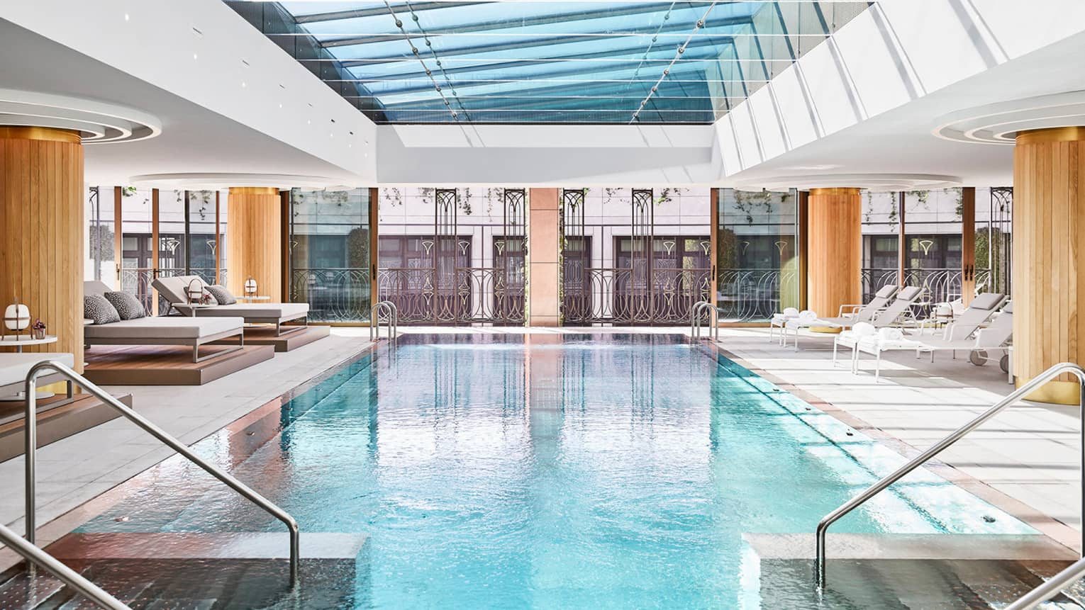 Rectangular indoor pool with two staircases into the pool, glass window ceiling