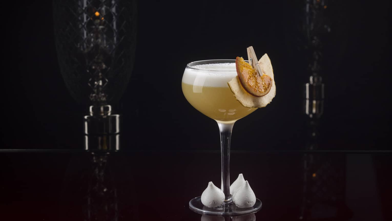 Cocktail glass with lemon garnishes against a black backdrop