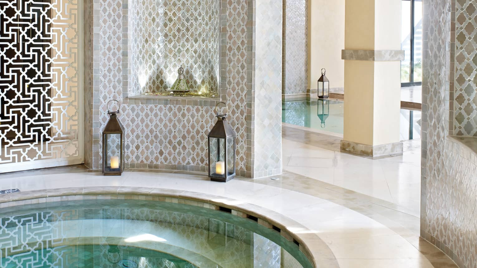 Small round whirlpool tub surrounded by decorative white detail wall, lanterns