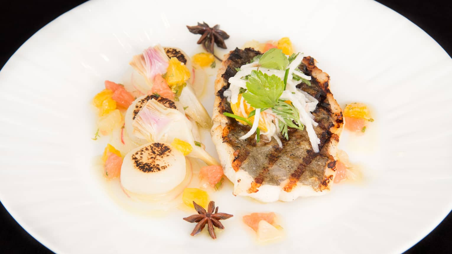 Grilled white fish filet and three seared scallops on plate with herbs, vegetable garnish