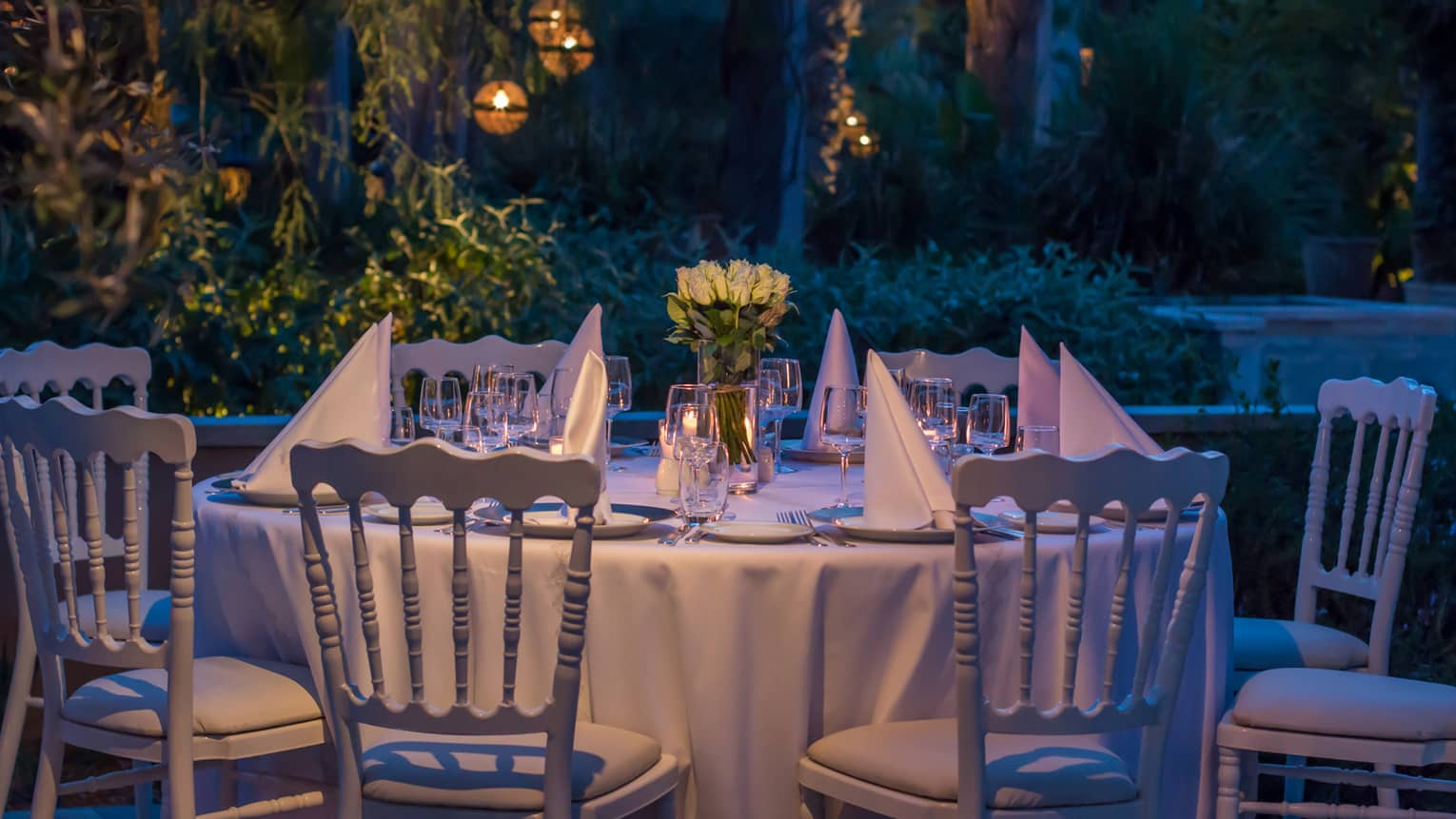 Folded white napkins on small round banquet dining table in garden at night