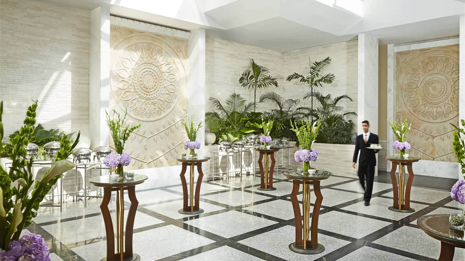 Server with tray walks through white marble room with accent tables, floral displays