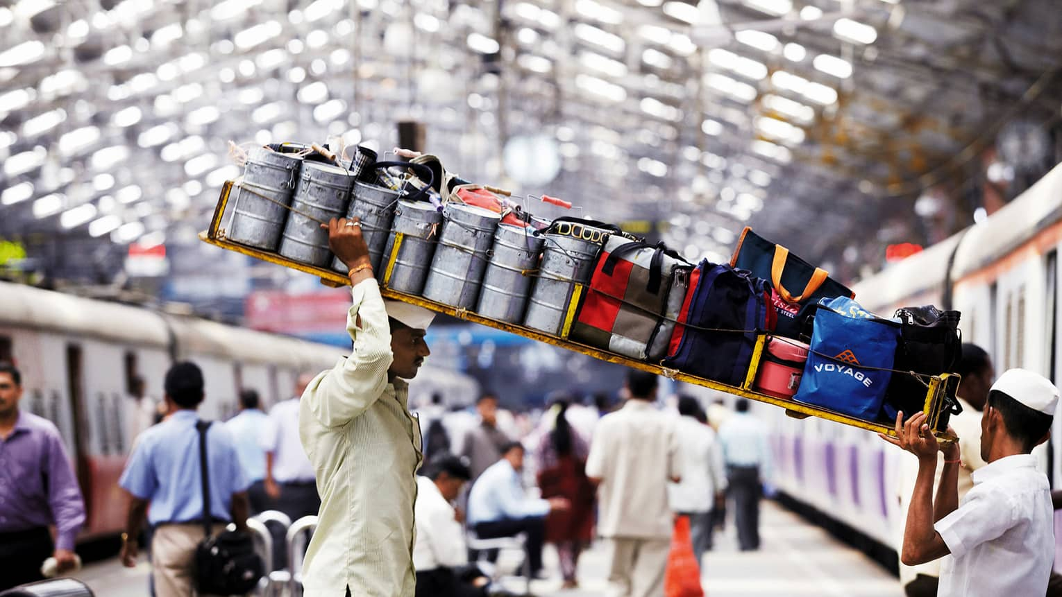 Dabbawalas lunchbox delivery men carry long tray with bags, cans through station