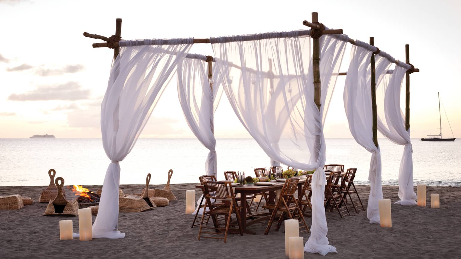 Sheer white curtains draped across wood posts around dining table on beach at sunset