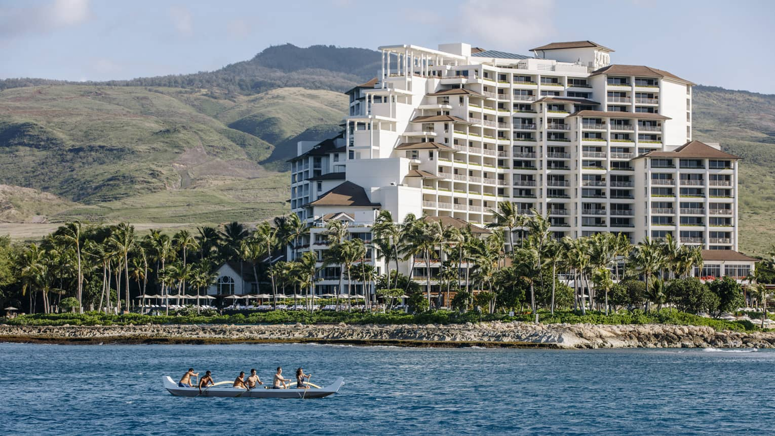 An outrigger canoe paddles past the Hotel