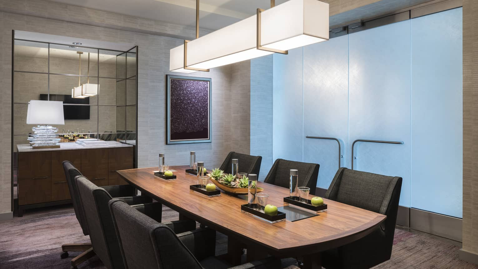 Wood boardroom meeting table with black executive chairs under modern light, glass wall