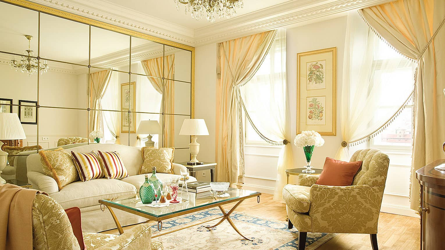 Duplex Suite living room sofas and chairs with gold accents, mirror panel wall with gold frame, bright windows, curtains