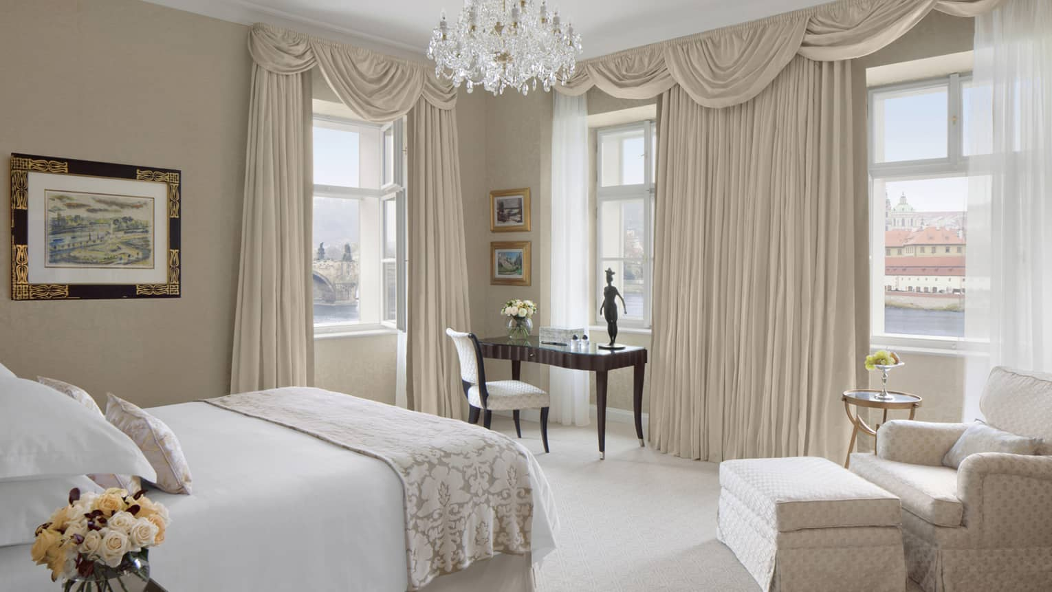 Room with white bed, tan club chair and ottoman, chandelier, tan curtains and desk