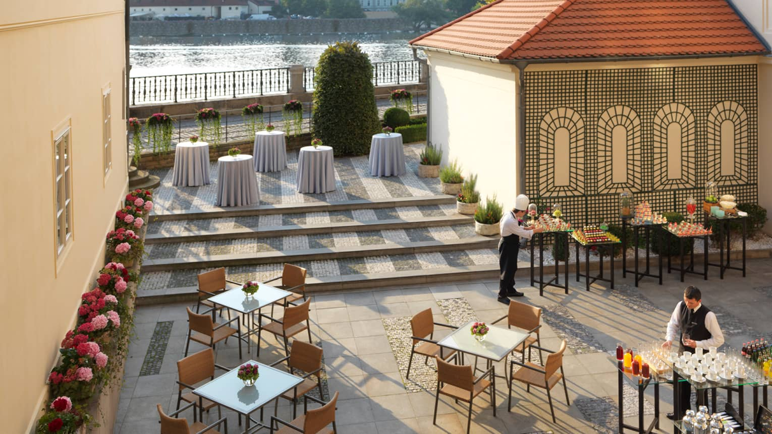 Aerial view of Karel Terrace patio tables and chairs, servers in uniforms prepare tables