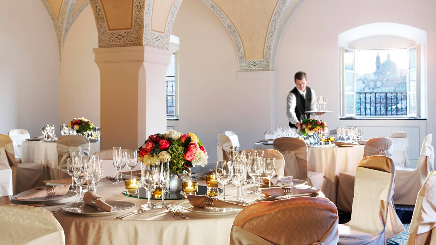 Server sets round formal banquet table under vaulted ceilings in Vltava Meeting Room