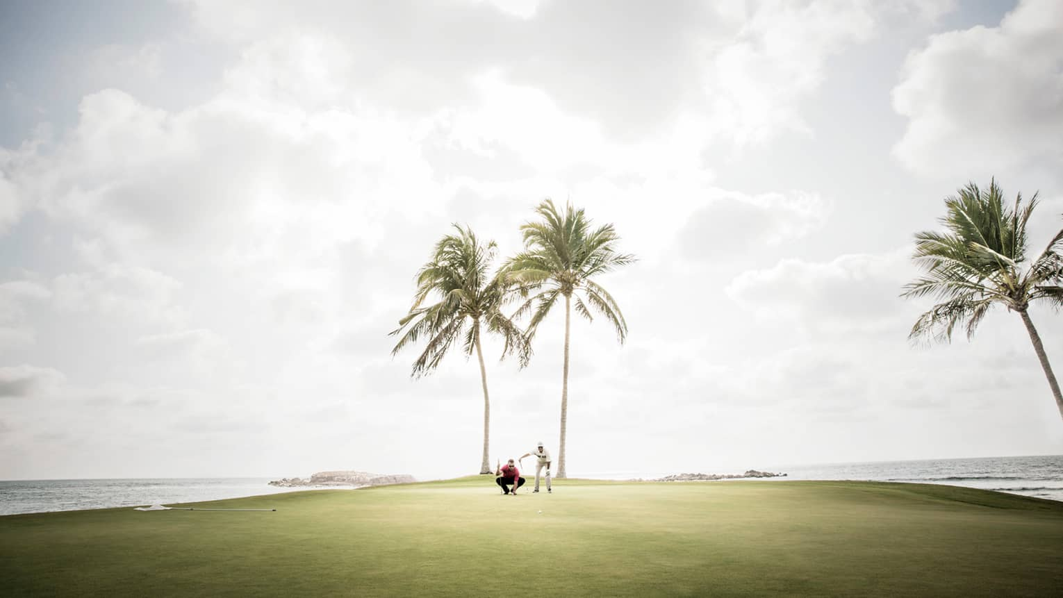 Two men kneel on golf green under two palm trees, ocean on each side