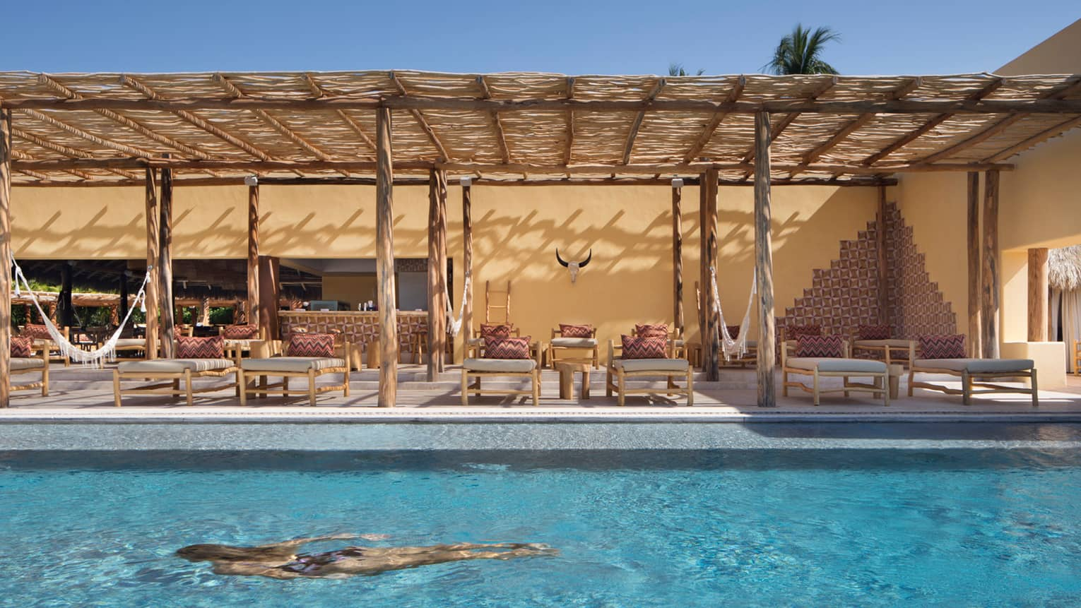 Woman swims in turquoise Tamai adults-only pool, lounge chairs under bamboo patio awning