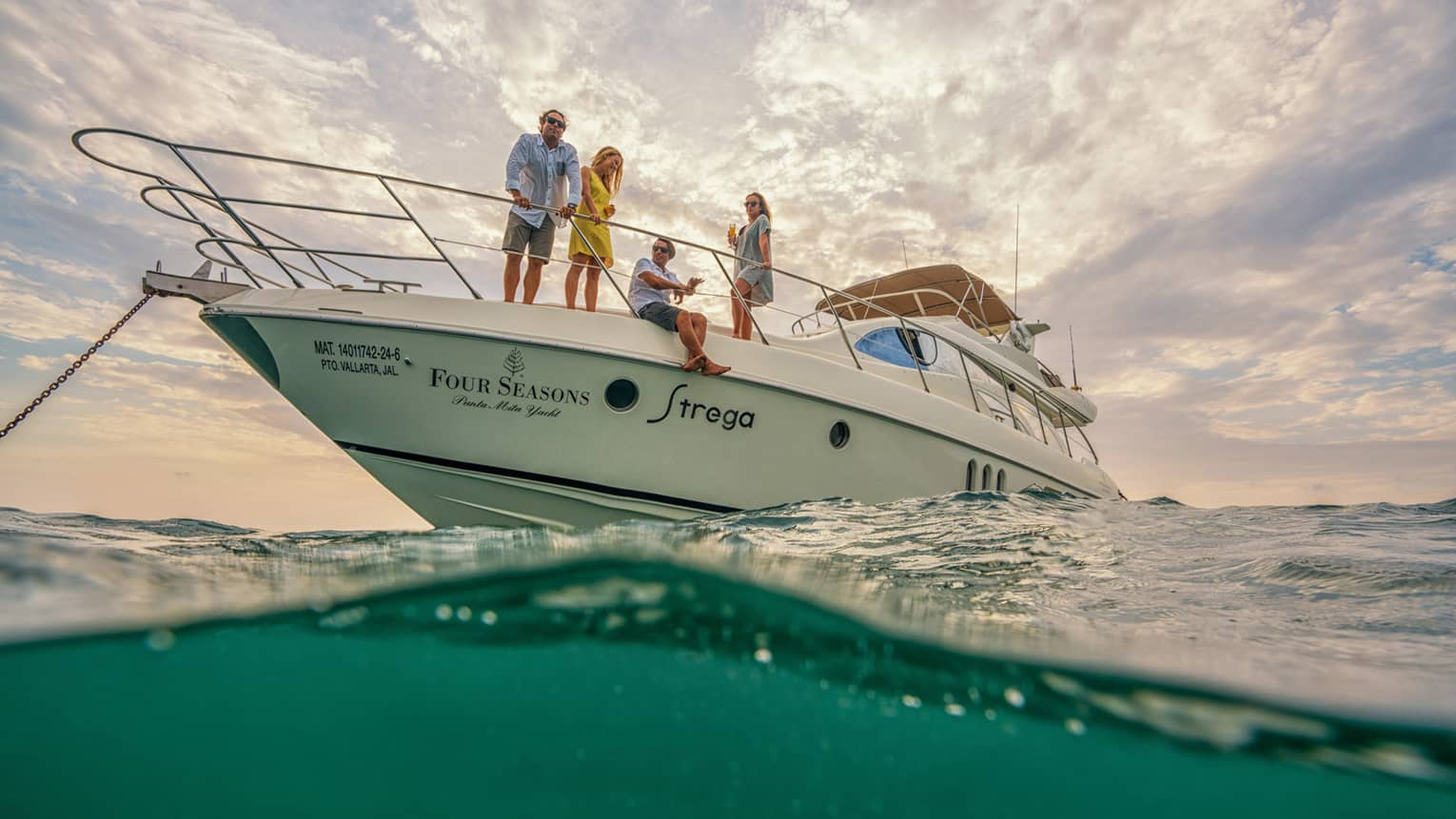 White Four Seasons motor yacht anchored in ocean, two men and two women look out at sea