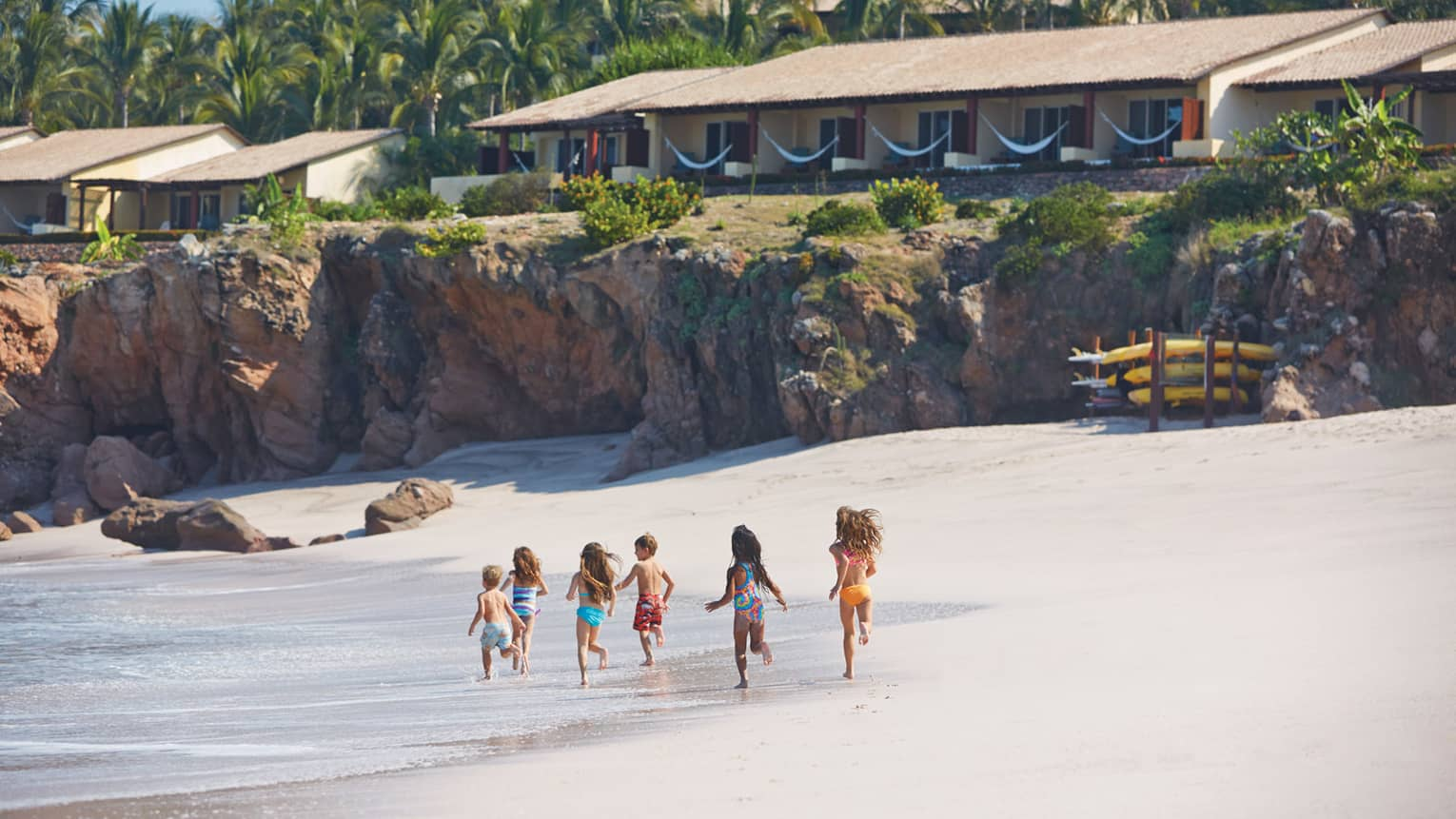Six young children in swimsuits run on white sand beach near water, resort casitas on cliffs above