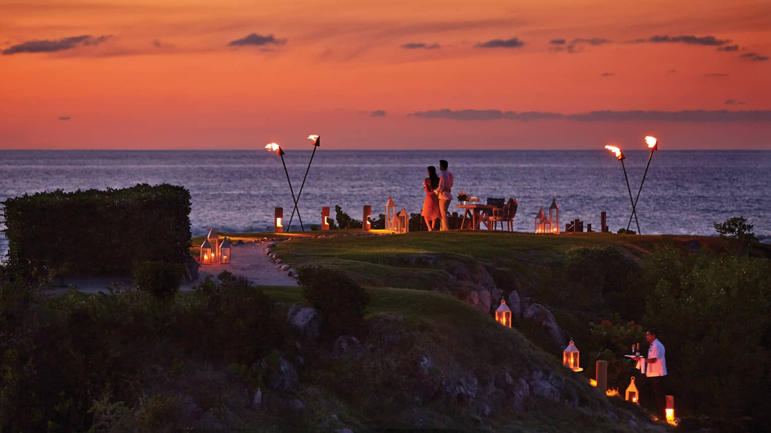 Couple stands on The Rock outpost at dusk, overlooking ocean with private dining table with lanterns, torches