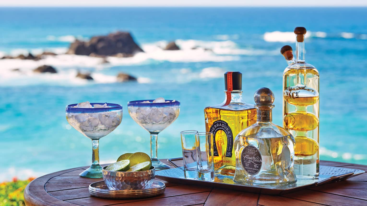 Close-up of Cora Lounge table, tray with tequila bottles, two margarita glasses with ice, bowl of limes