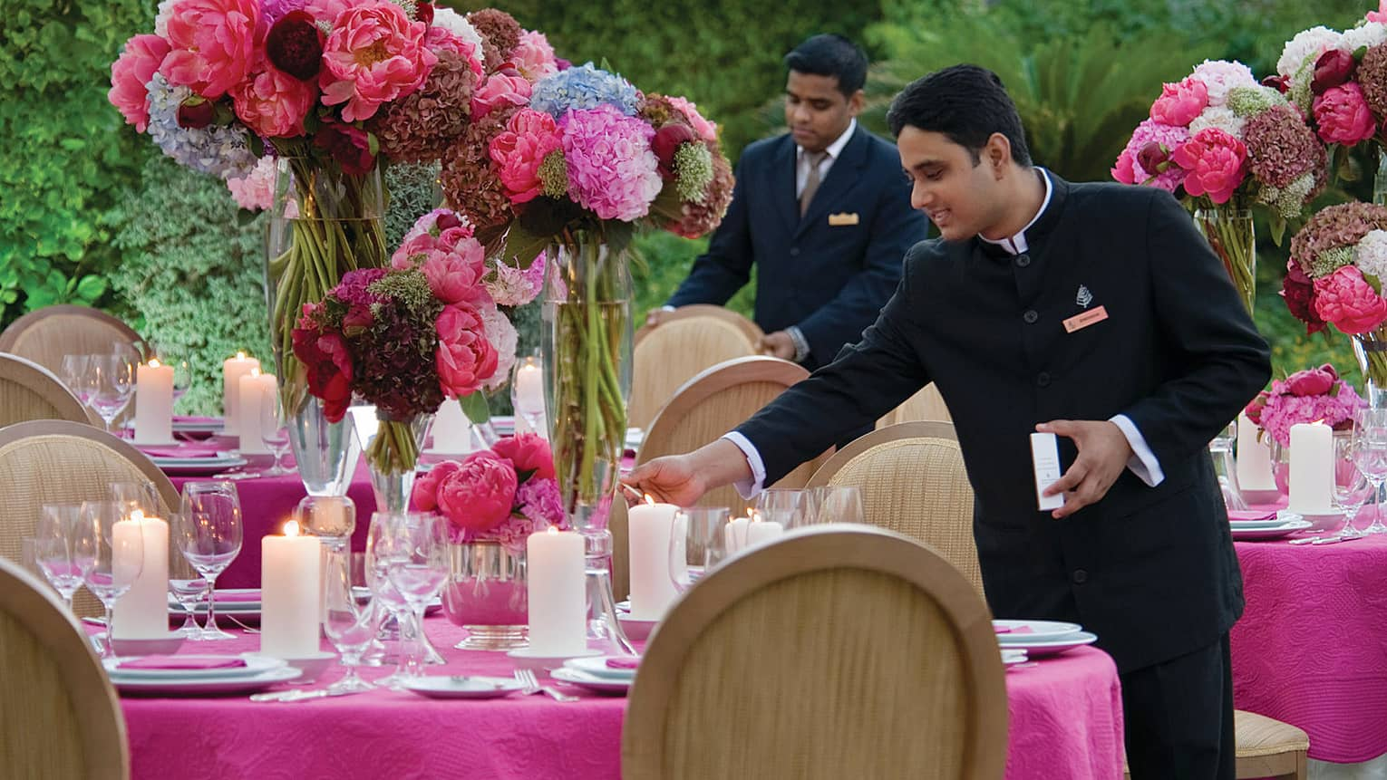 Two male staff set table with pink tablecloth, large vases of flowers and candles