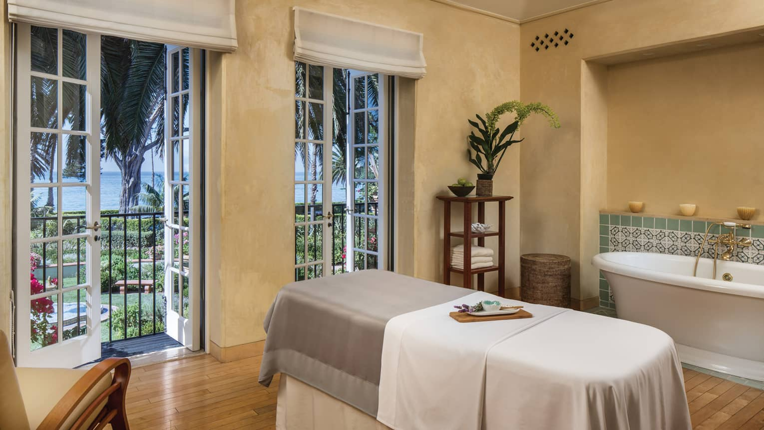 A spa treatment room with massage table, bath tub, wooden floors, French doors to a garden