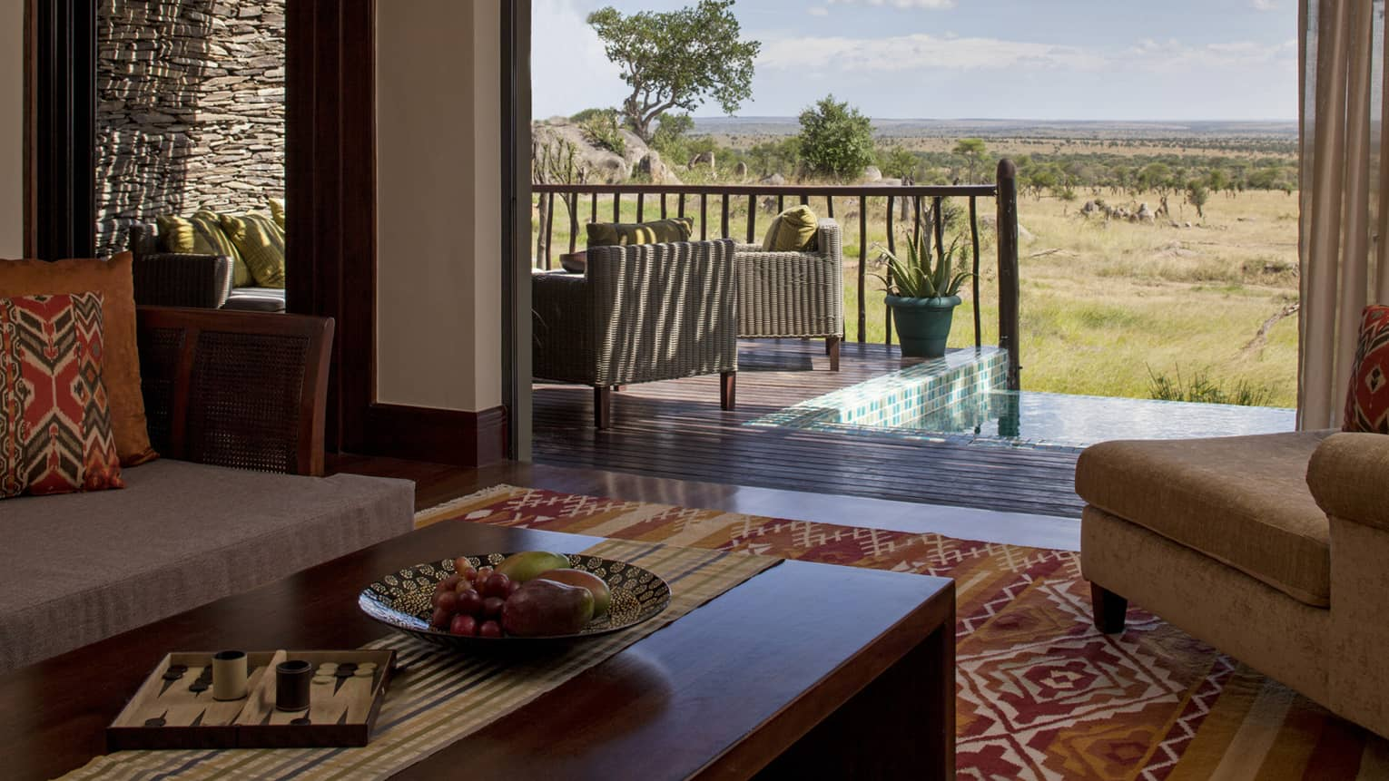 A suite decorated with earth toned couches and a rug look out onto an out at the watering hole