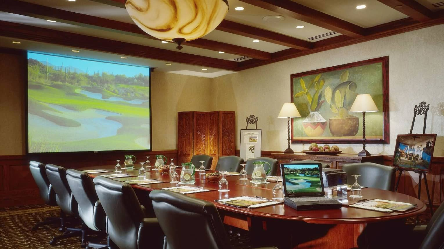 Laptop on large boardroom table facing projector screen with golf course image, under marble lamp