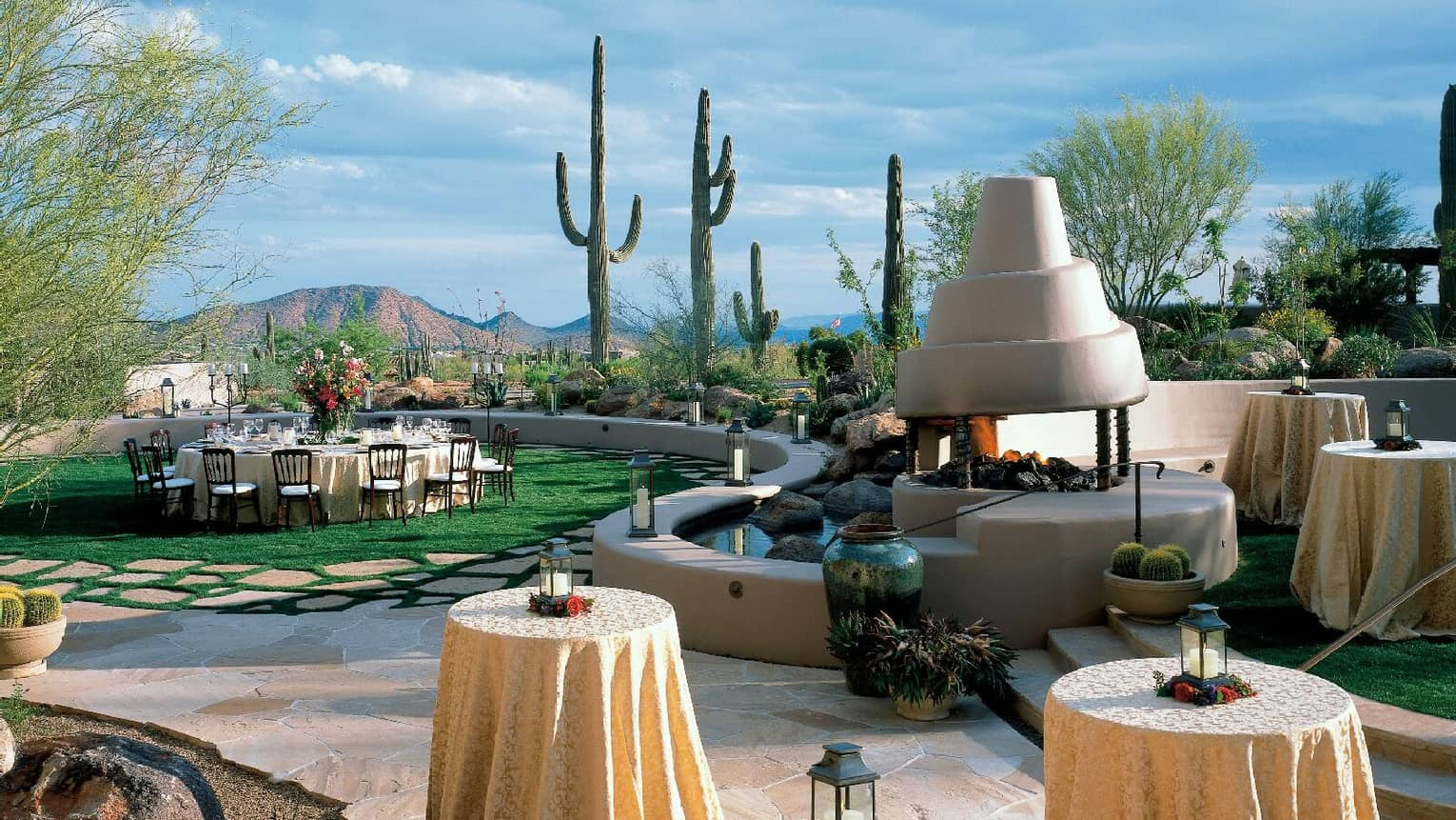 Troon Lawn reception tables on sunny lawn by spiral fireplace and wall, tall cacti