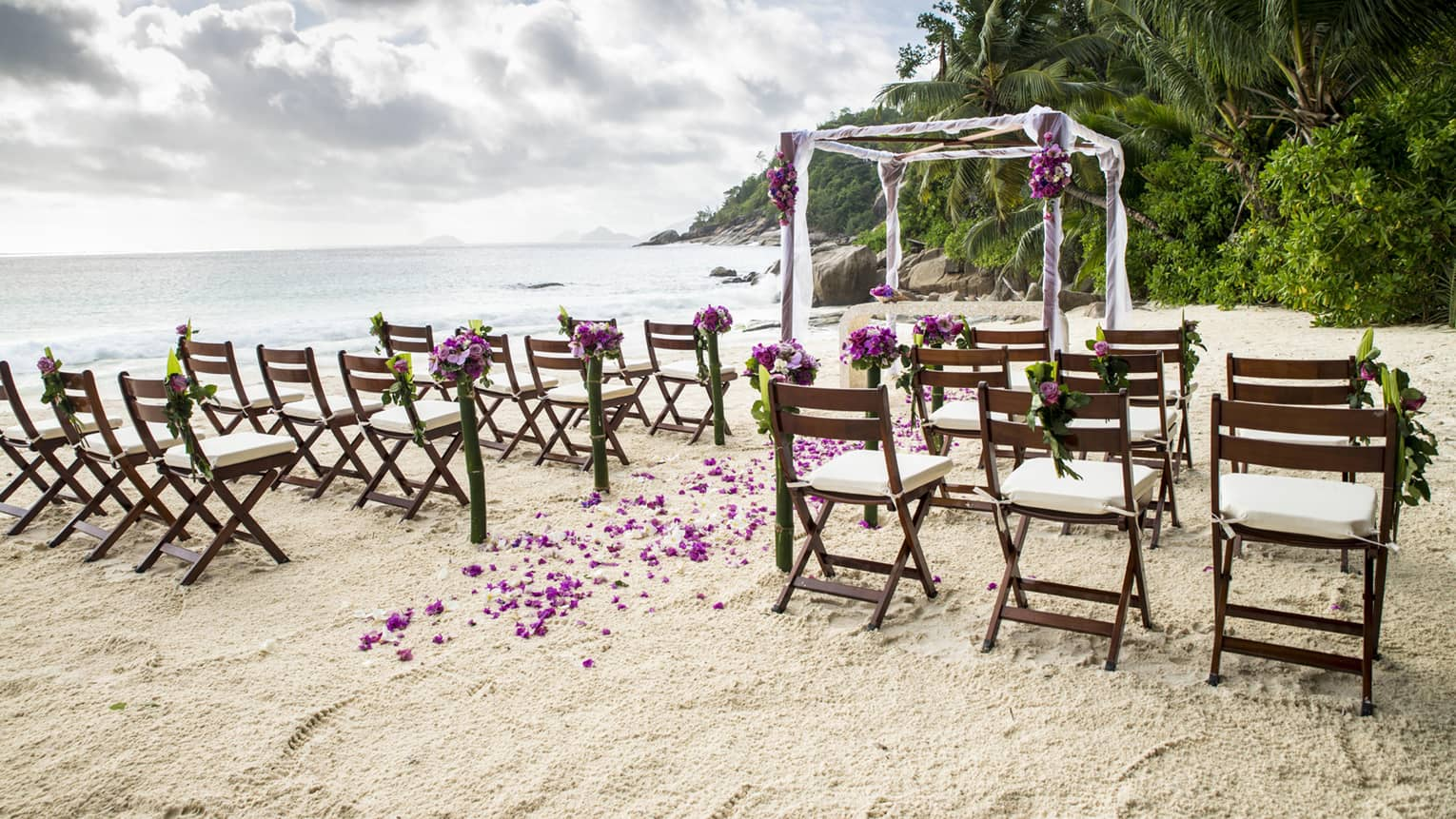 Rows of wooden chairs on sand in front of canopy decorated with purple flowers by ocean