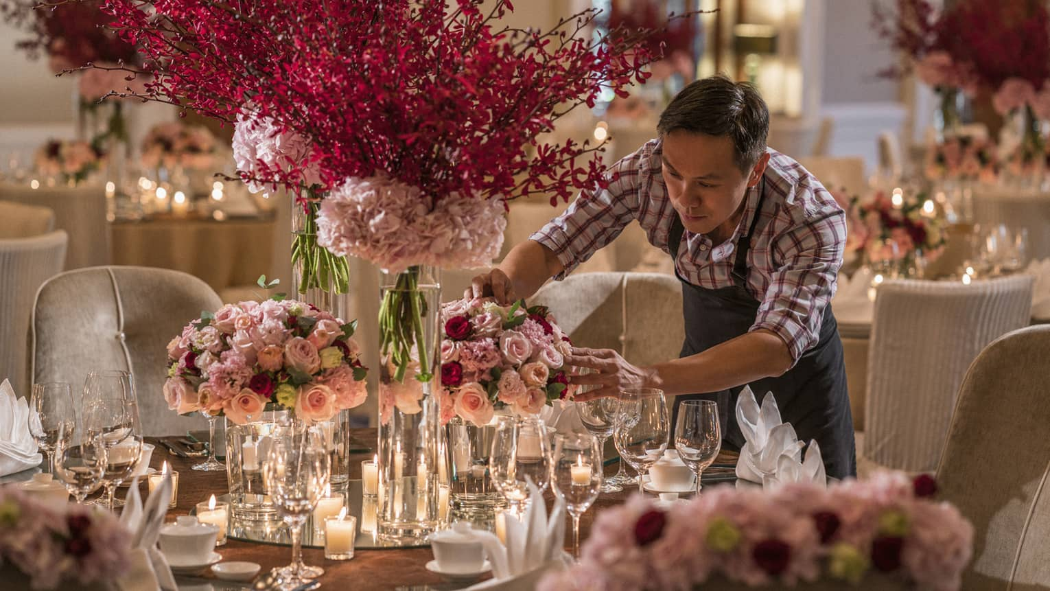 Hotel staff arranges roses in vase on large candle-lit banquet table