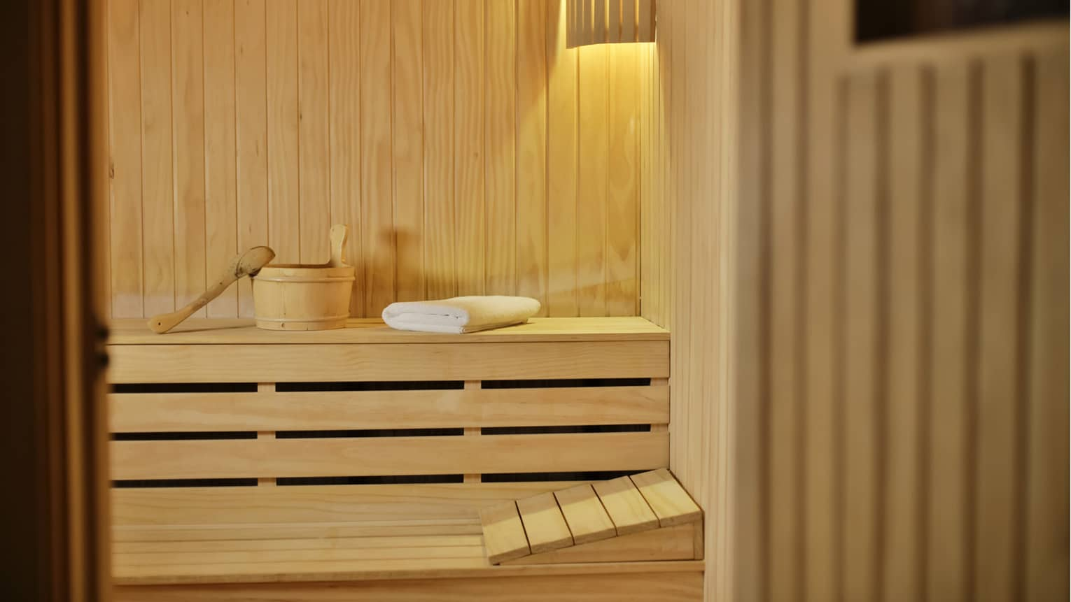 Wood basket and folded towel on bench in spa sauna steam room