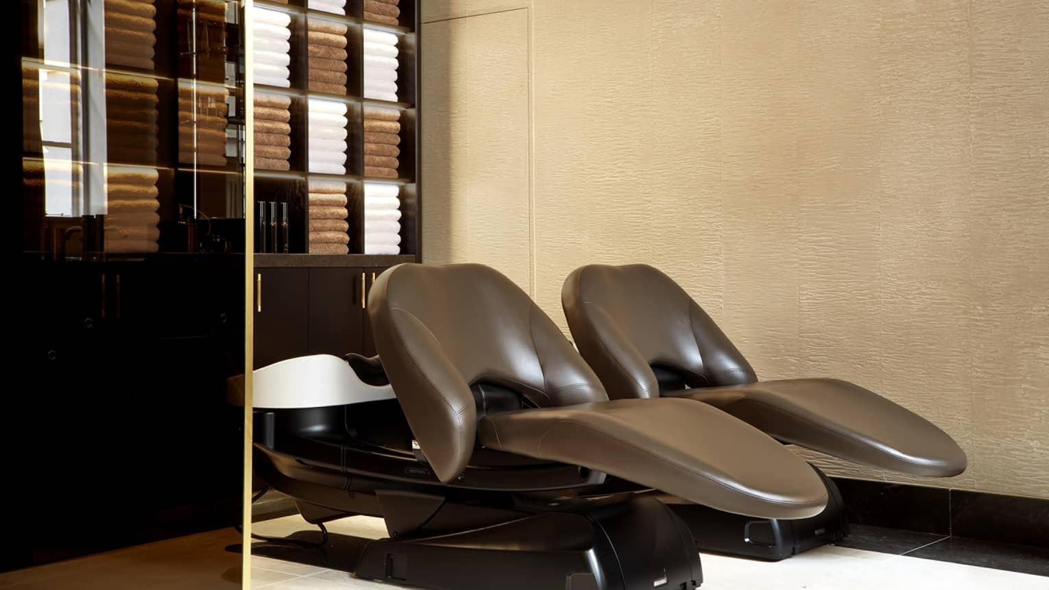 GiellyGreen salon with warm-toned brown leather reclining chairs