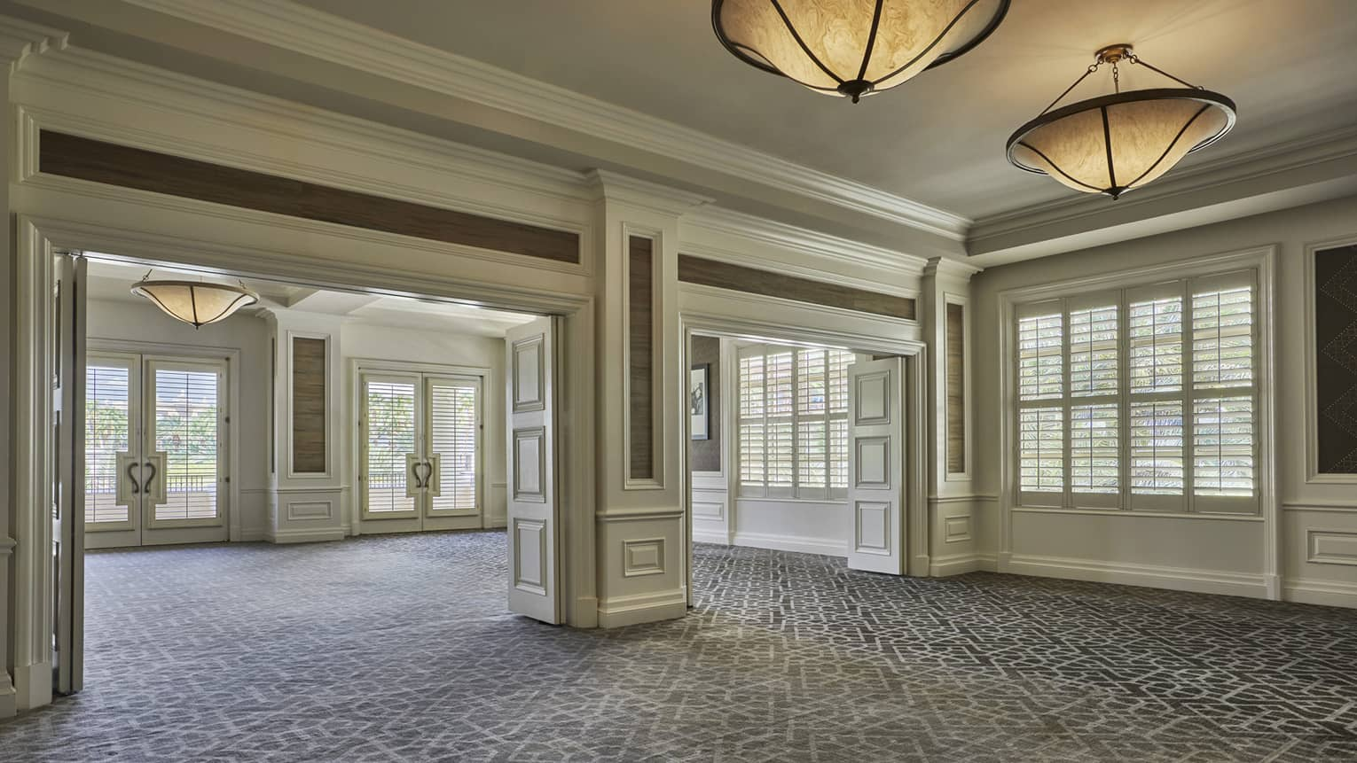Mesquite event space, open carpeted room with sunny windows, large ceiling lights
