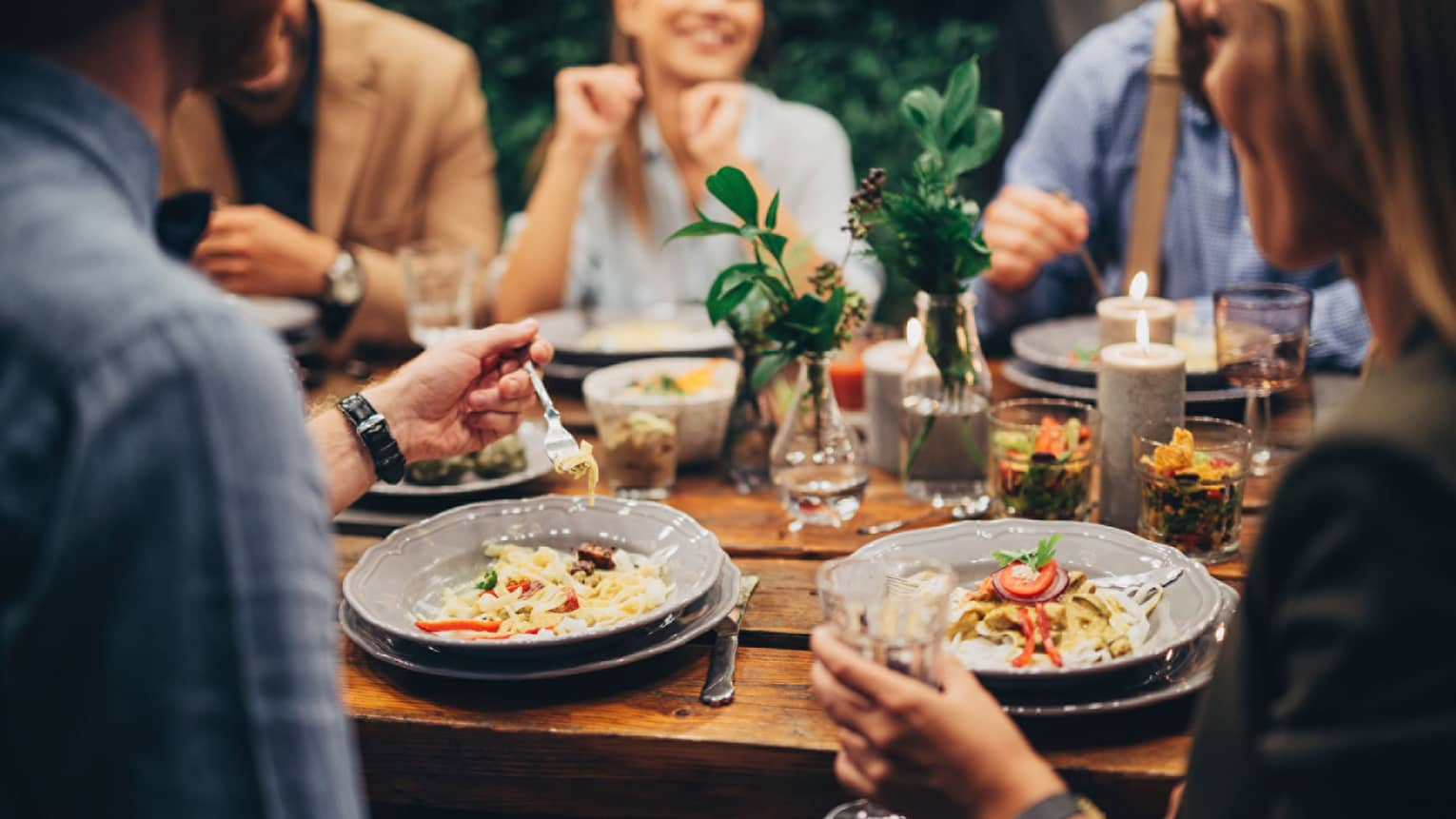 Close-up of group of friends around gourmet pasta dishes on outdoor table