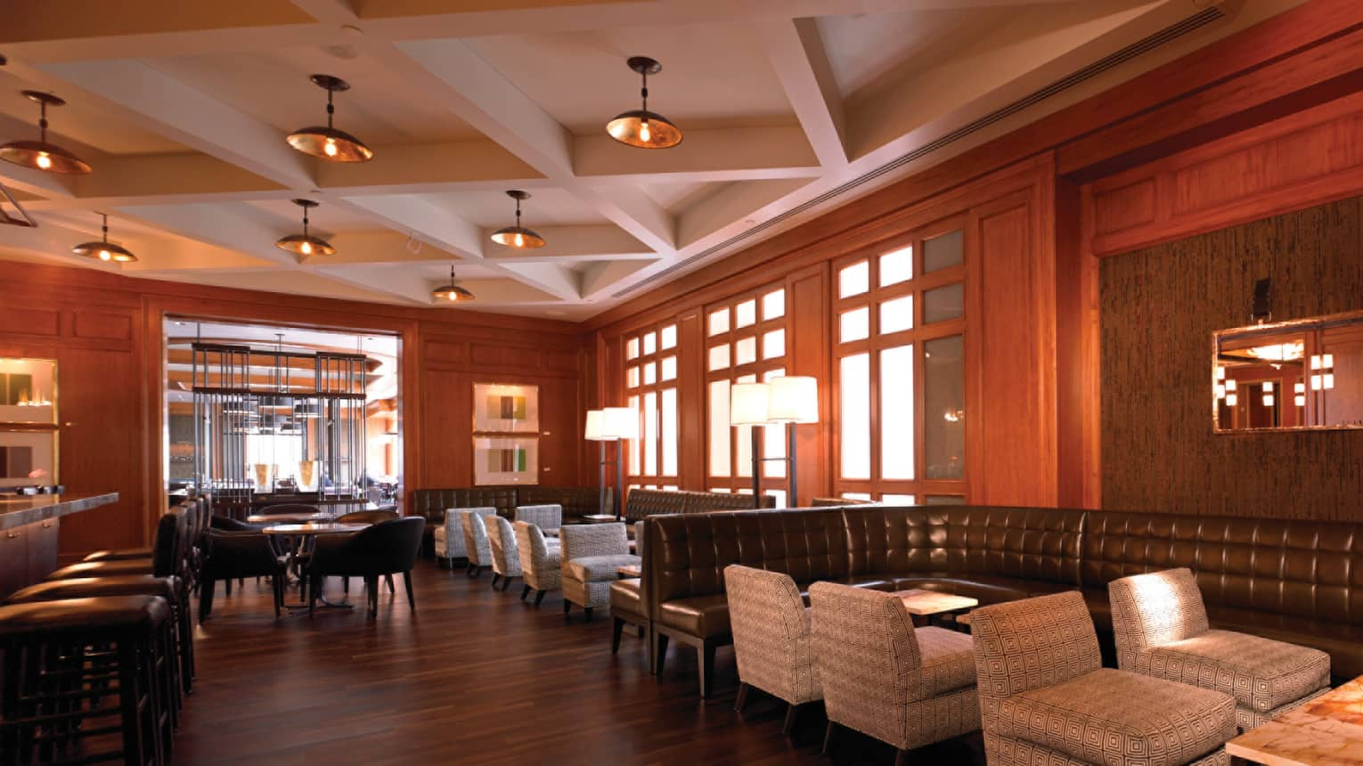 MKT Restaurant dining room with dark wood floors and walls, brown leather benches, plush chairs
