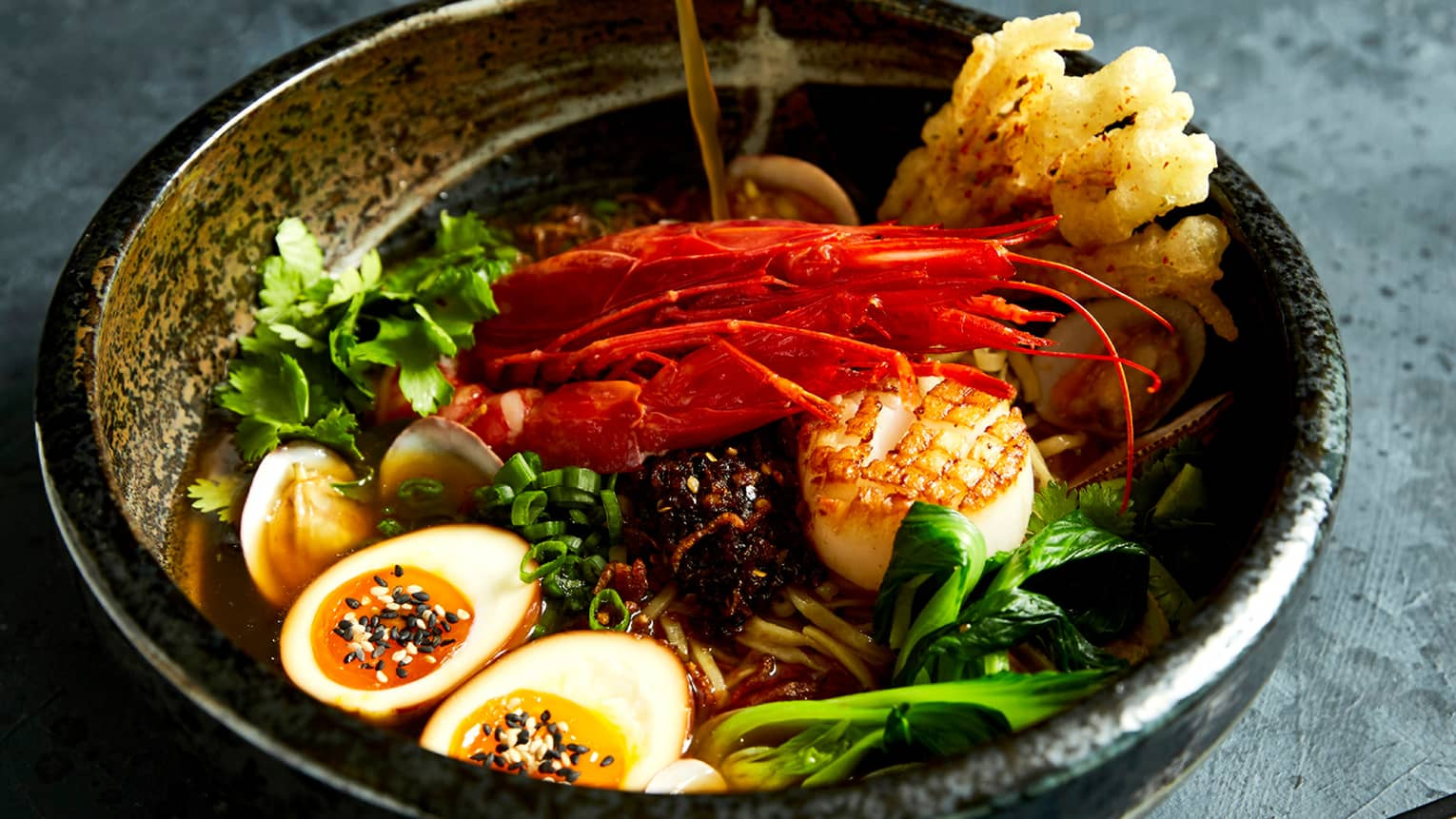 A brass bowl holding poached eggs, lobster claws, scallions and greens