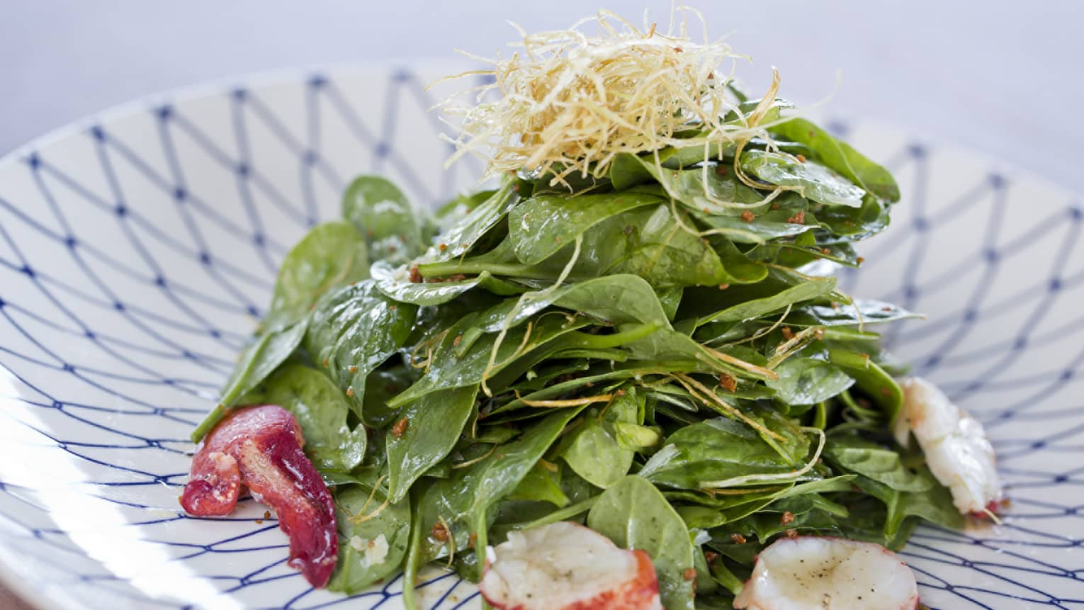Close-up of Brittany Lobster and Baby Spinach Salad on blue and white patterned dish