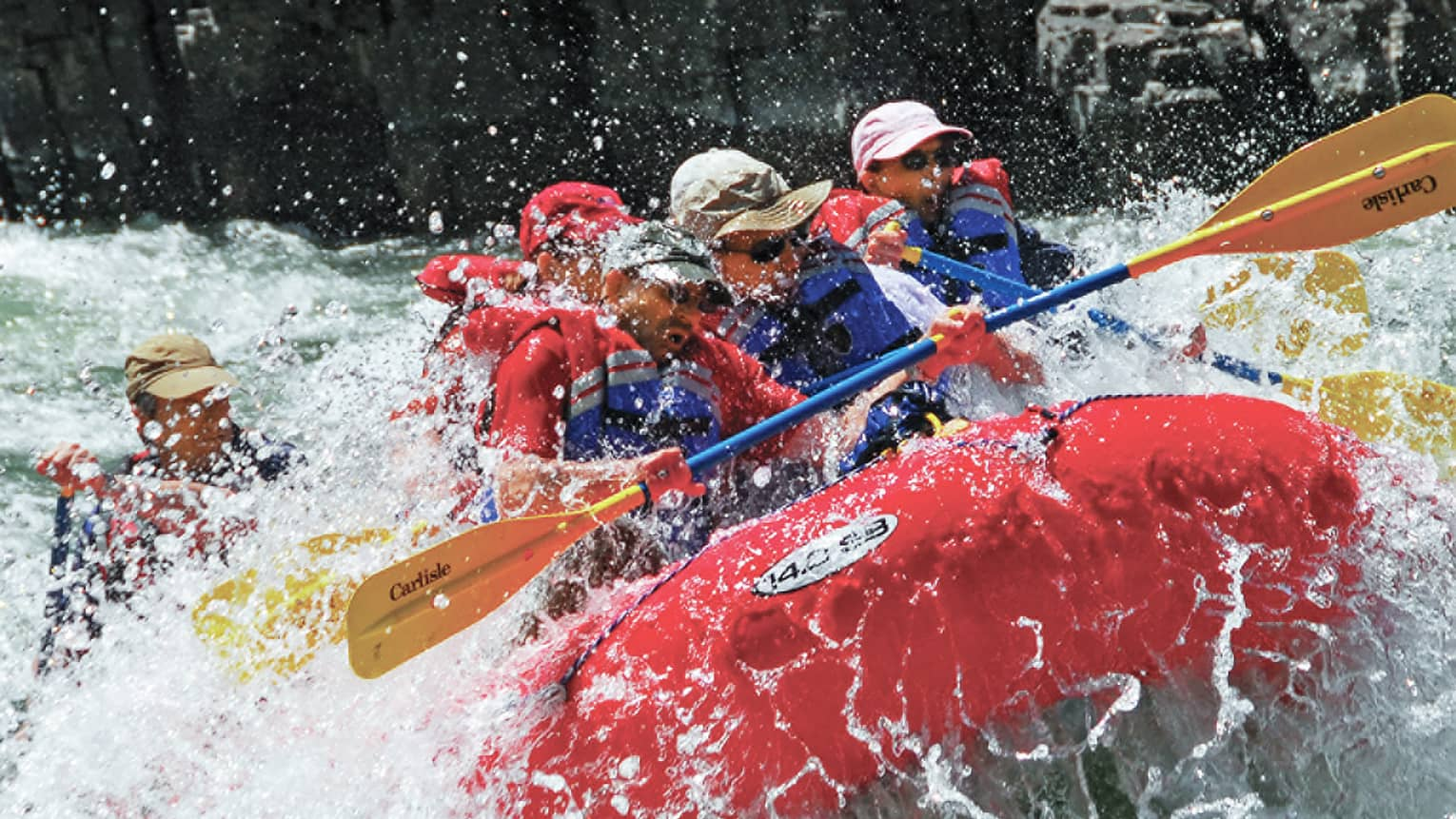 Water sprays around red inflatable raft, people with paddles, life vests white water rafting