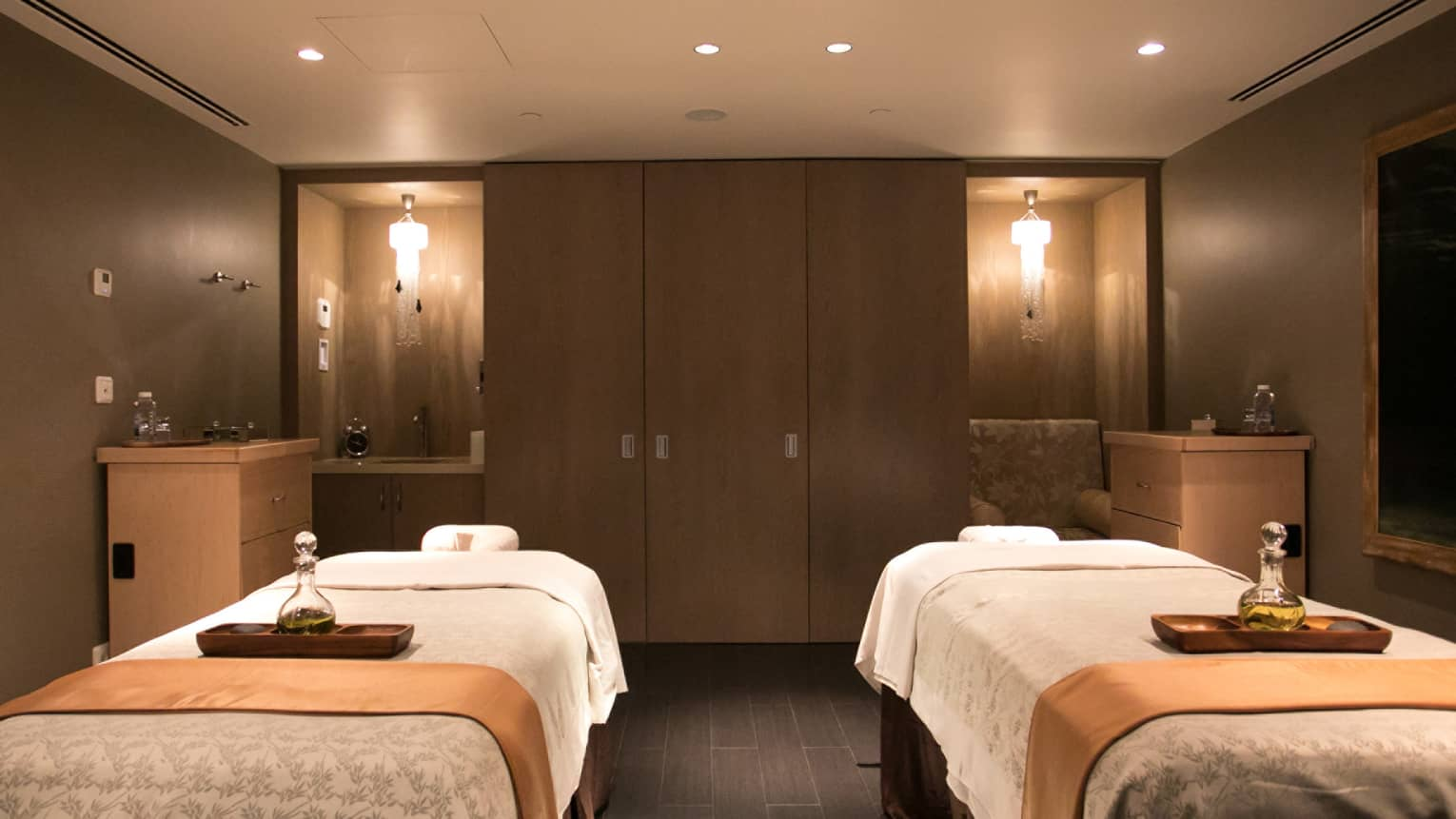 Two massage beds side-by-side in Luceo Spa couple suite with low lighting, wood cabinets