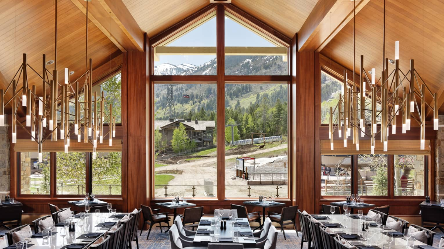Dining room with long tables, chandeliers on either side, giant wood-framed window with a view of the mountains