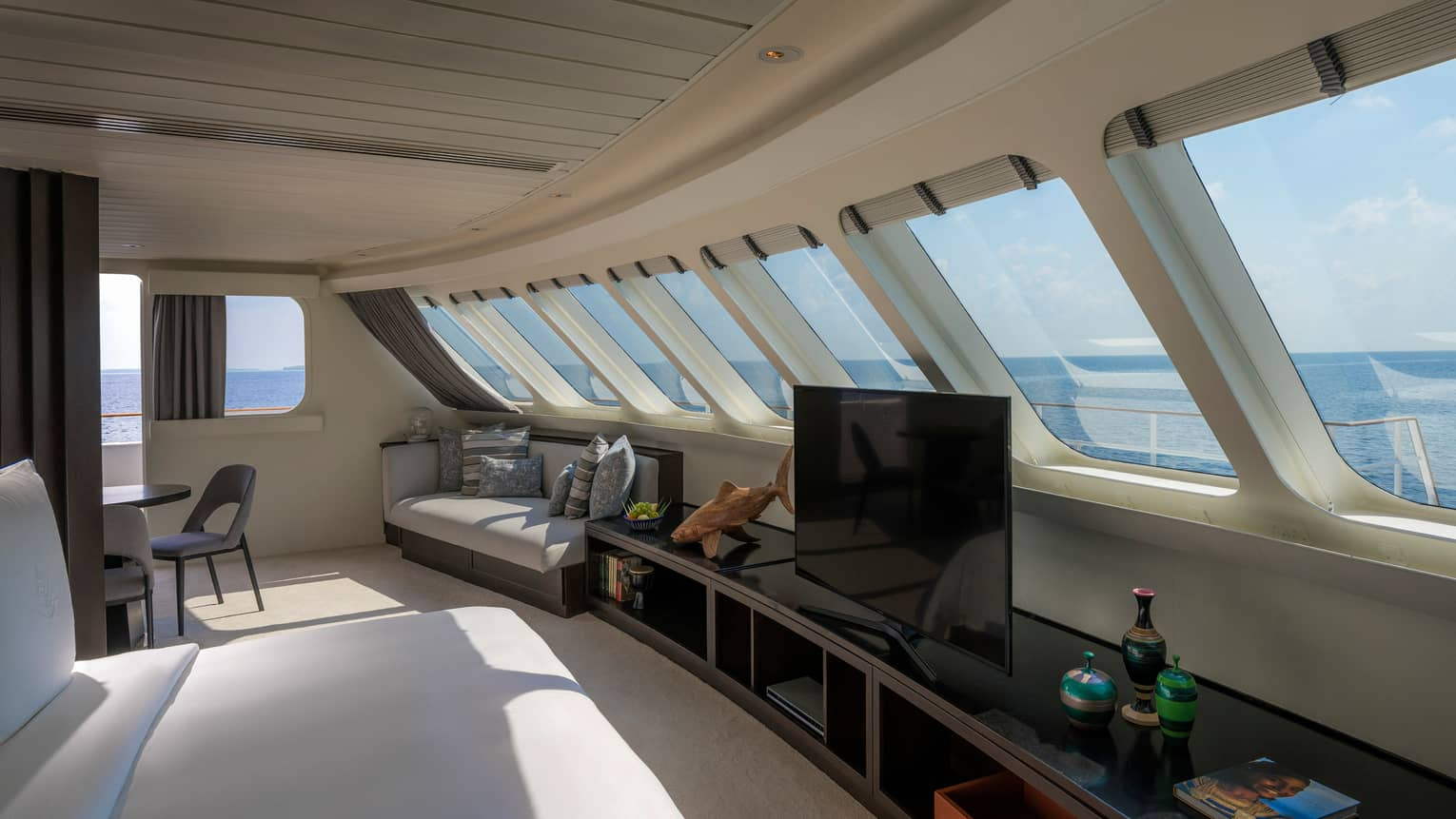 Seating area inside yacht with row of curved windows, dresser with TV, bench