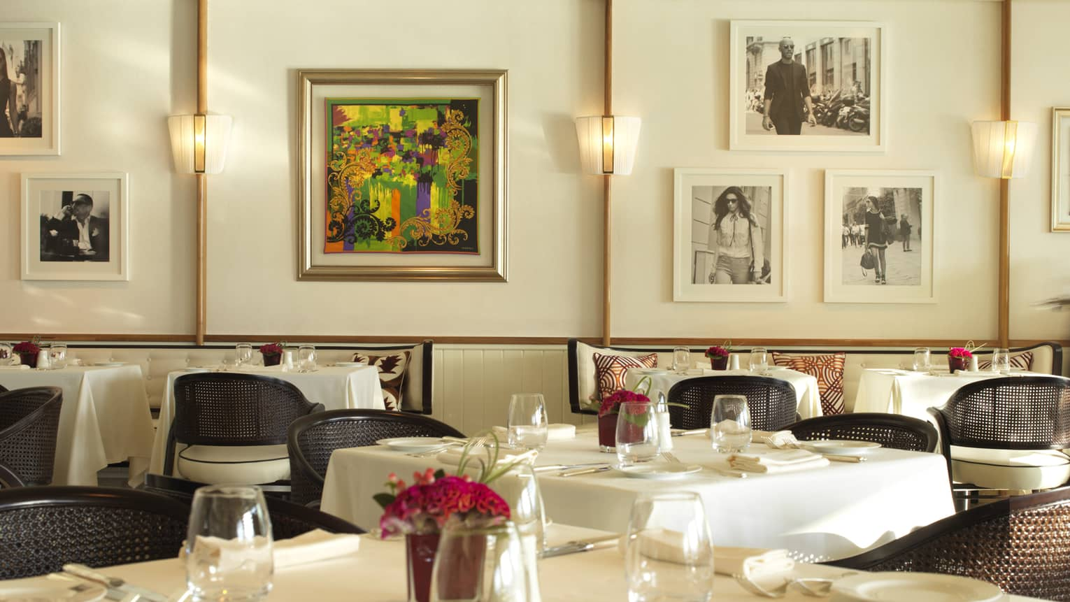 Server in blue suit walks through Cafe Milano dining room with elegant white dining tables, colourful art, framed black-and-white photos