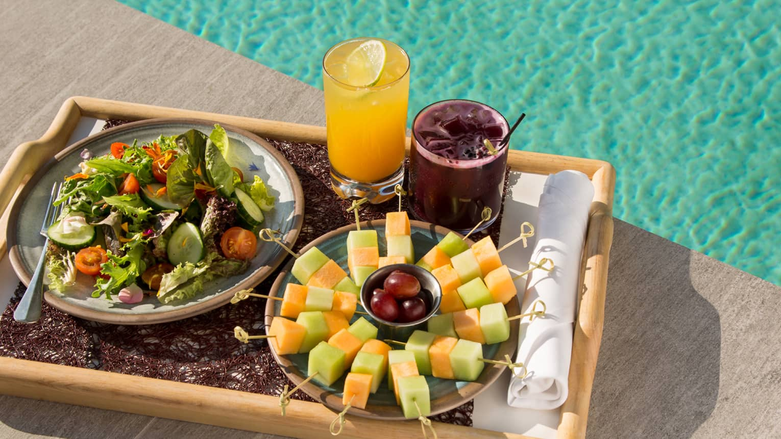 Tray with fresh fruit skewers, fresh salad, juices on tray beside swimming pool