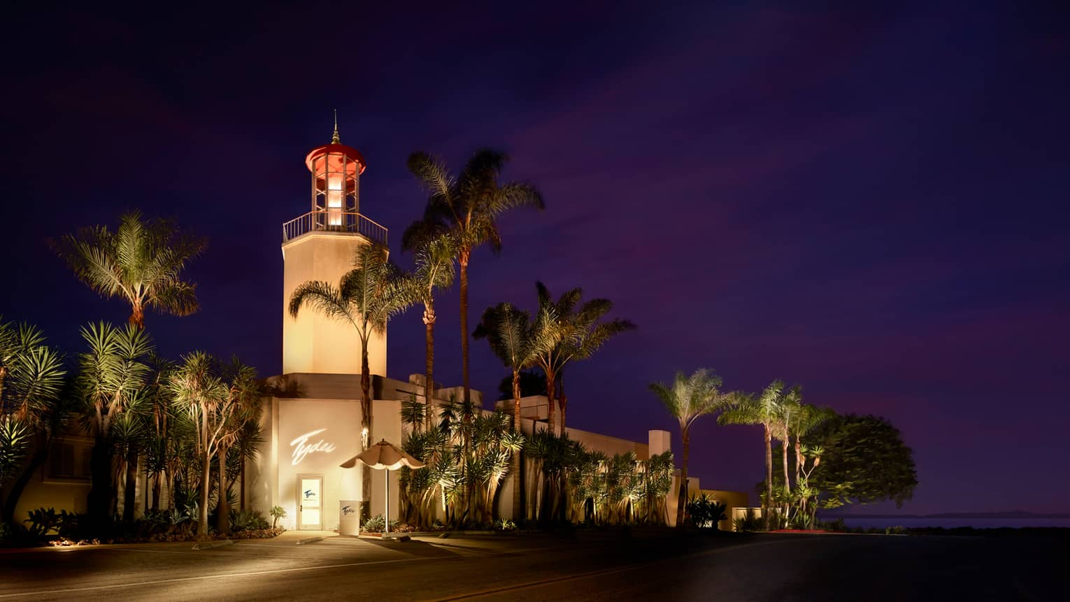 Tydes exterior at night with glowing tower, tall palm trees