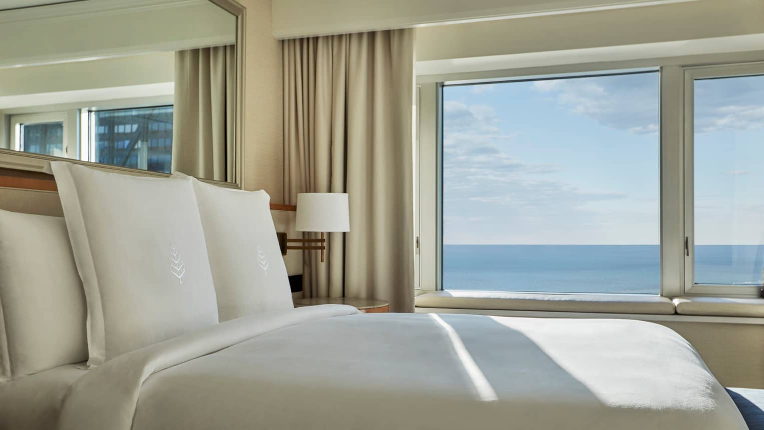 Close-up of hotel bed with white linens, Four Seasons logo by sunny window overlooking Lake Michigan