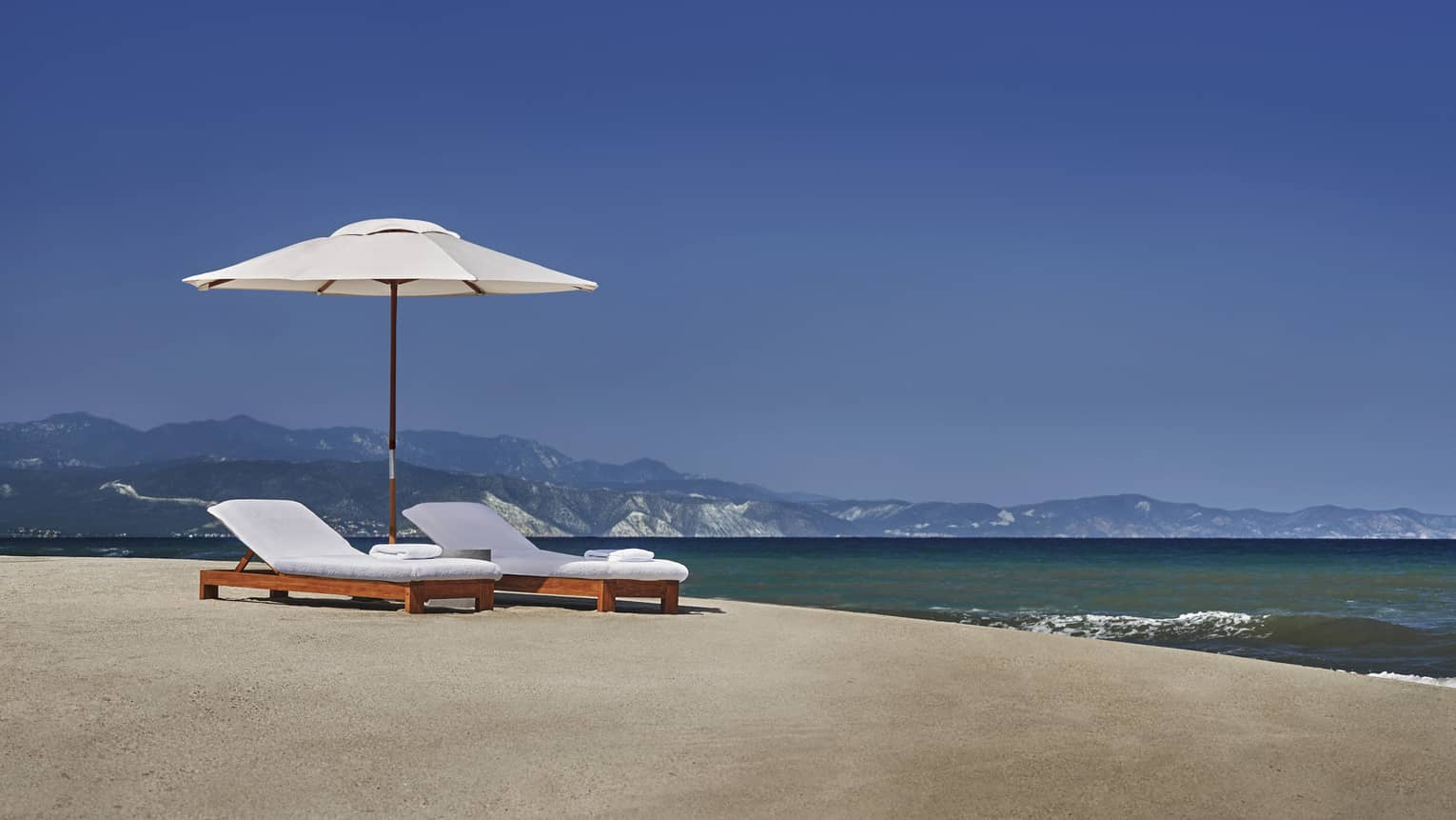 White patio umbrella, lounge chairs on sand beach