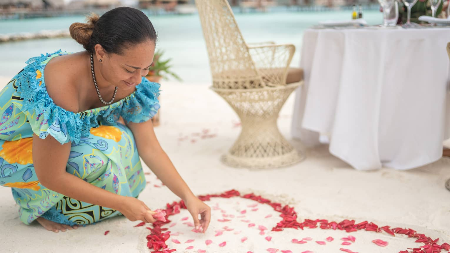 Woman arranges red rose petals into heart shape on sand beach