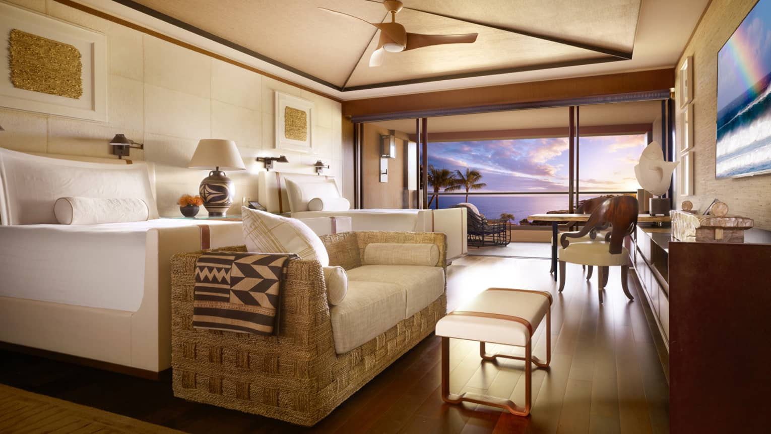 Ocean-View Room bed with loveseat, table at foot by open wall to balcony, sunset